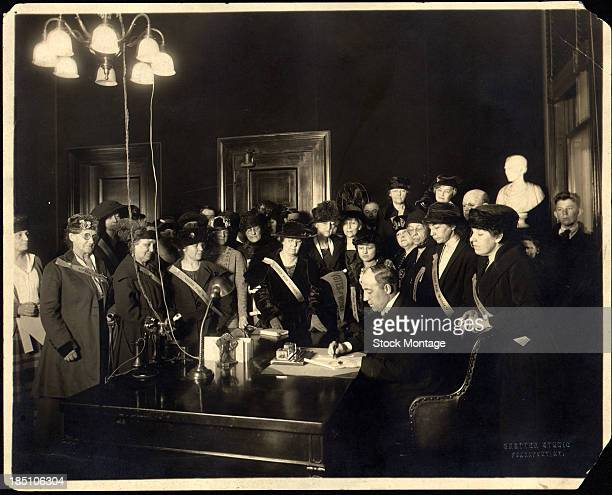 Surrounded by mostly women many with 'Votes for Women' sashes American politician Governor of Kentucky Edwin P Morrow signs his states ratification...