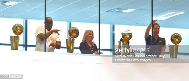 Surrounded by NBA championship trophies Lakers President Earvin Magic Johnson left owner Jeanie Buss and GM Rob Pelinka right look down at the media...