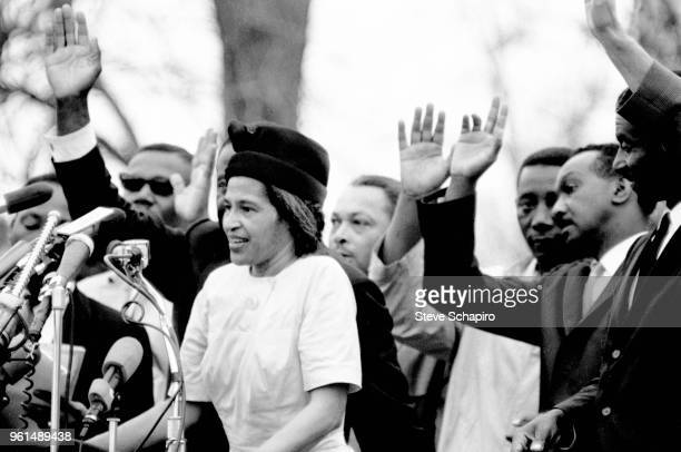 Surrounded by others with raised hands, American Civil Rights activist Rosa Parks speaks in front of the Montgomery State Capitol building at the...