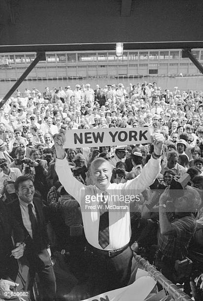 Surrounded by photographers and onlookers American politician and threeterm mayor of New York City Ed Koch holds up a sign that reads 'Nwe York' at...