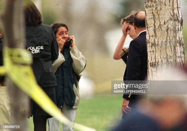 Surrounded by police officers an unidentified Columbine High School student in Littleton CO makes a phone call following a shooting spree at the...