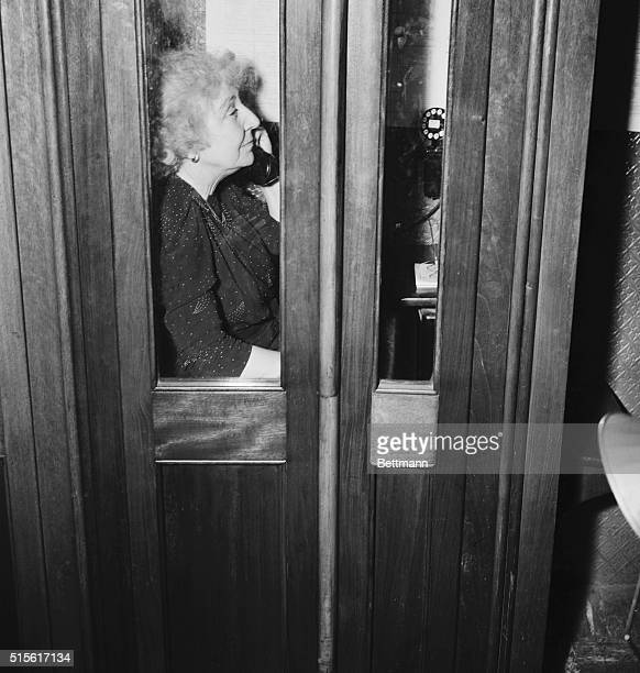 Surrounded by reporters and photographers after casting her lone vote against war with Japan Miss Rankin ducked into a phone booth in the House...
