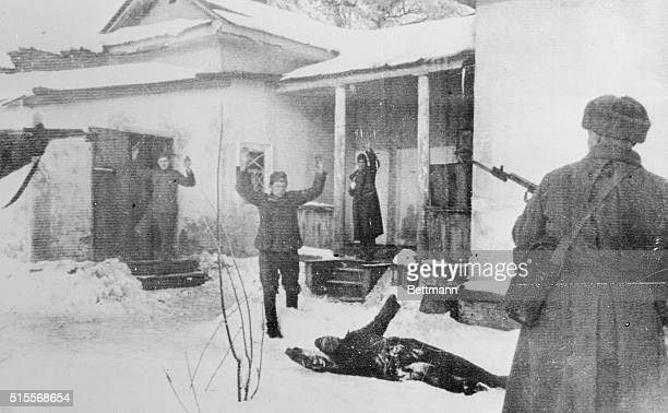Surrounded by Russian soldiers German troops come out of a house in the Kharkov area in this Russian censored photo radioed from Moscow to London...