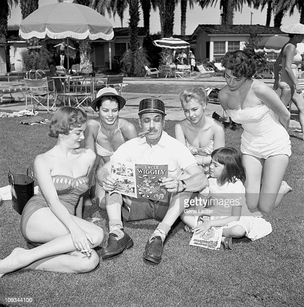 Surrounded by several unidentified woman in bathing suits and one young girl Possibly his daughter Melinda Marx American comedian and actor Groucho...