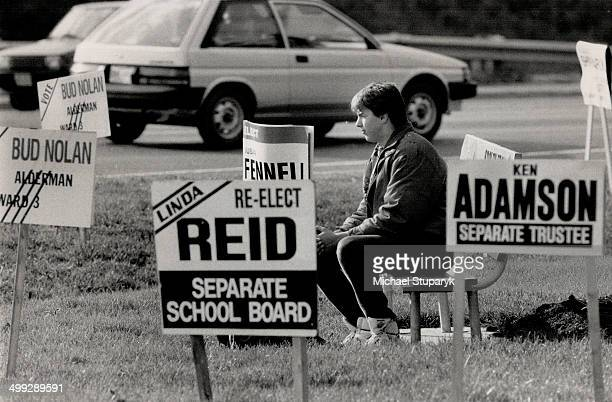 Surrounded by signs Brian Smith of Brampton may be ponder his choices in the Nov 14 municipal election while taking a break at the corner of Highway...
