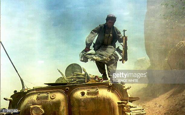 Surrounded by smoke from an incoming artillery shell explosion a soldier loyal to Afghan President Burhanuddin Rabbani abandons his BMP1 armored...