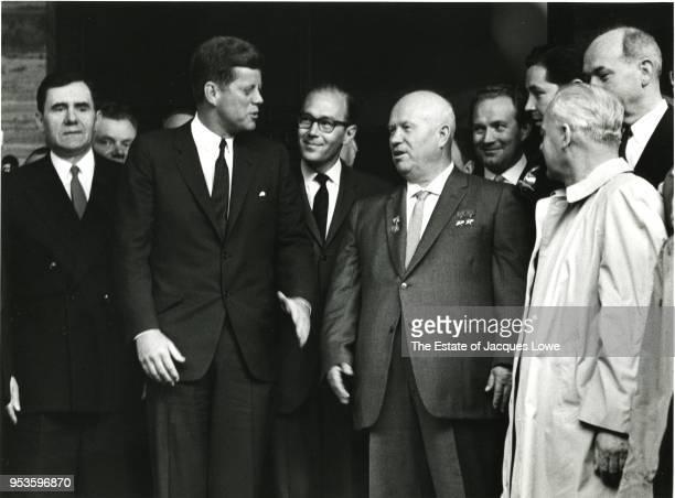 Surrounded by staffers US President John F Kennedy and Soviet Premier Nikita Khrushchev speak on the steps outside American Embassy Vienna Austria...