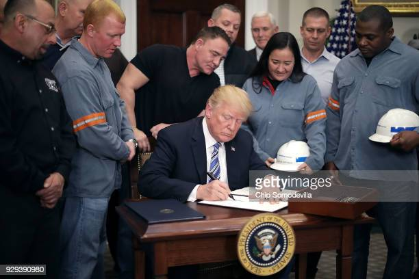 Surrounded by steel and aluminum workers US President Donald Trump signs a 'Section 232 Proclamation' on steel imports during a ceremony in Roosevelt...