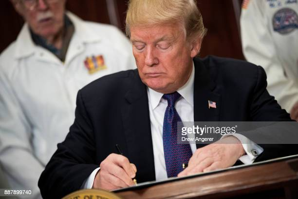 Surrounded by survivors of the 1941 attack on Pearl Harbor President Donald Trump signs a proclamation for National Pearl Harbor Remembrance Day in...