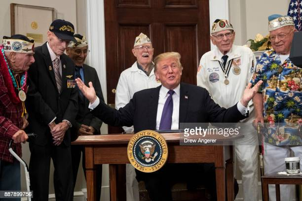 Surrounded by survivors of the 1941 attack on Pearl Harbor President Donald Trump gestures after signing a proclamation for National Pearl Harbor...