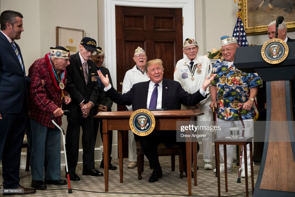 Surrounded by survivors of the 1941 attack on Pearl Harbor, President Donald Trump gestures after signing a proclamation for National Pearl Harbor Remembrance Day, in the Roosevelt Room of the White House, December 7, 2017 in Washington, DC. Thursday is the 76th anniversary of the attacks against the Hawaii naval base.