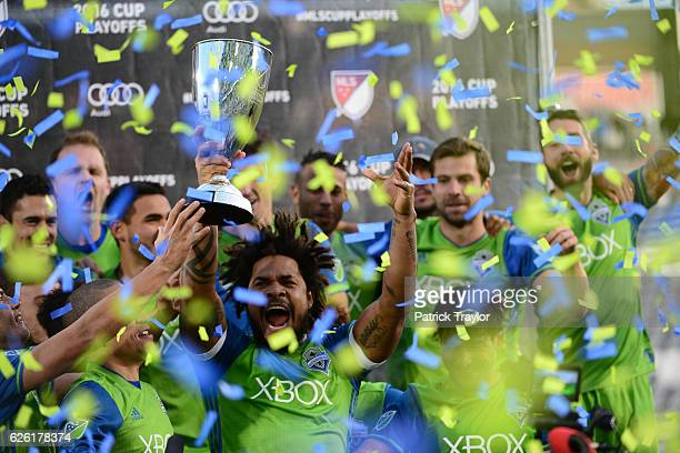 Surrounded by teammates and confetti Roman Torres of Seattle Sounders holds up the MLS Western Conference trophy after the match The Colorado Rapids...