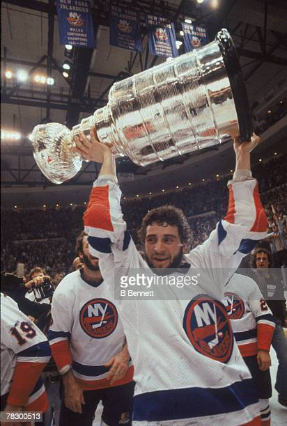 Surrounded by teammates Canadian ice hockey player Duane Sutter of the New York Islanders holds aloft the Stanley Cup on the ice after his team's...