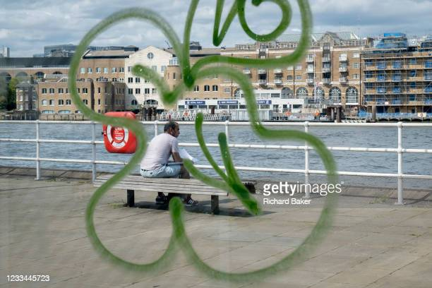 Surrounded by the swirl of sprayed graffiti, a man sits reading on a bench overlooking the Thames river, at Butler's Wharf, on 11th June 2021, in...
