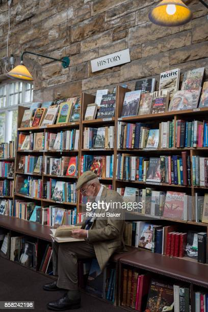 Surrounded by used books is an elderly gentleman reading a title the the shelves of the secondhand bookshop 'Barter Books' in the Northumbrian town...