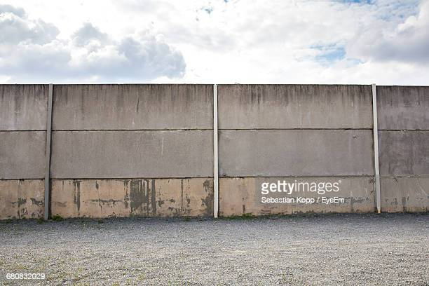 Surrounding Wall On Ground Against Cloudy Sky