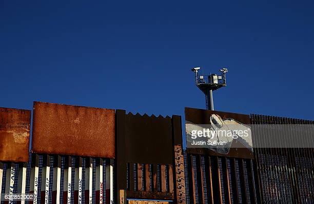 Surveillance cameras stand above the USMexican border fence at on January 27 2017 in Tijuana Mexico US President Donald Trump announced a proposal to...