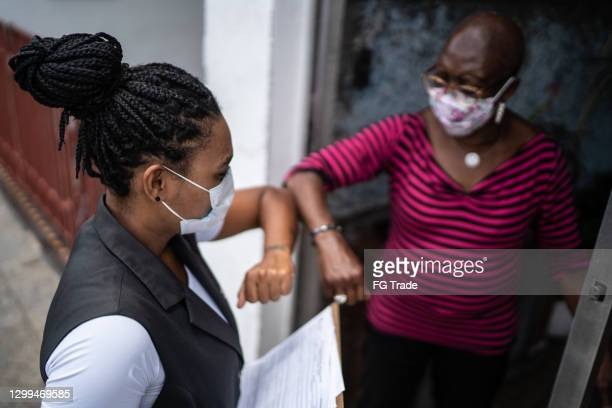 surveyor greeting senior woman in the doorway - wearing face mask - census stock pictures, royalty-free photos & images