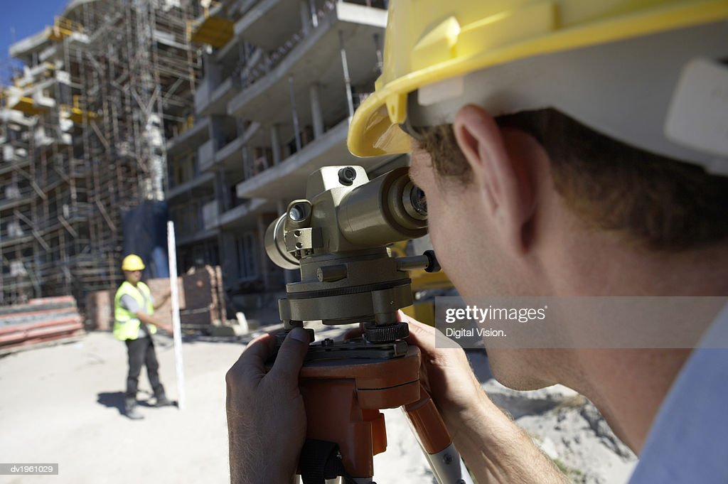 Surveyor Looking Through a Theodolite, on a Building Site : Stock Photo