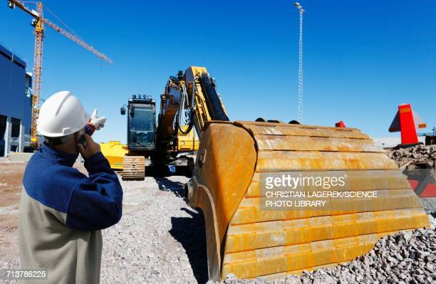 Surveyor on construction site with bulldozer