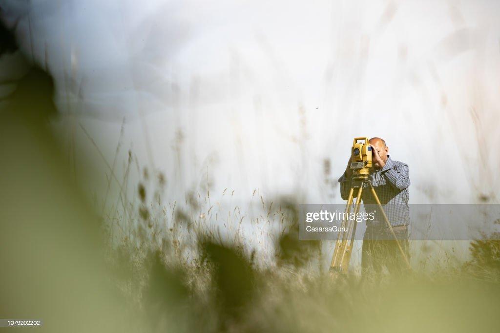 Surveyor Using Theodolite to Measure Land : Stock Photo