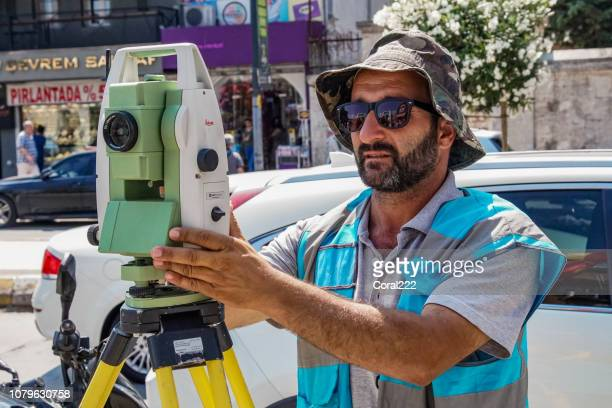 surveyor worker with theodolite in istanbul - cartography stock photos and pictures
