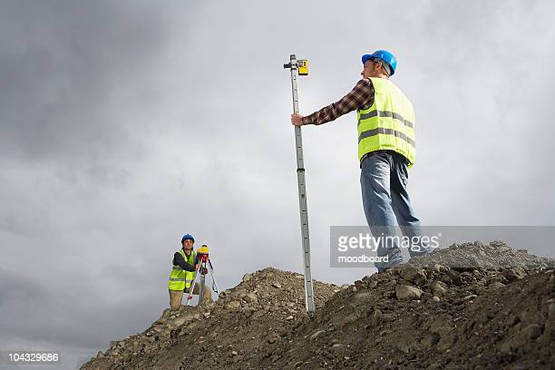 Surveyors using theodolite on building site