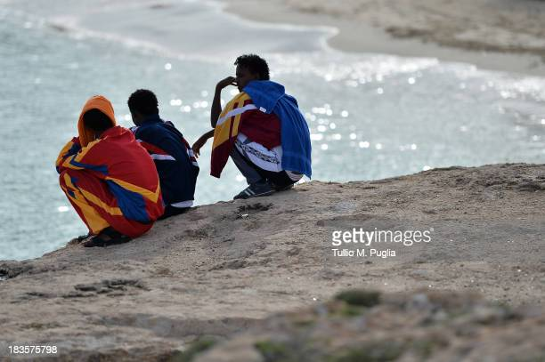 Surviving African immigrants from Thursday's boatwreck tragedy off Lampedusa island look on at Guitgia Beach on October 7 2013 in Lampedusa Italy The...