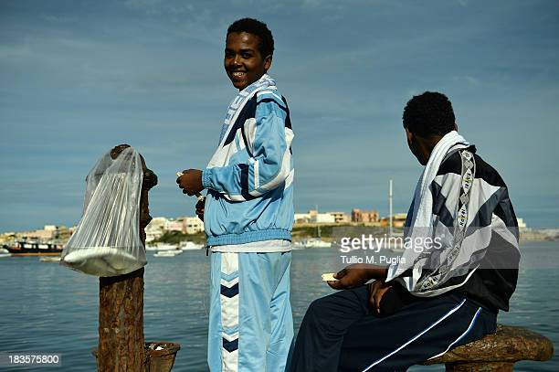 Surviving African immigrants from Thursday's boatwreck tragedy off Lampedusa island fish in the harbour on October 7 2013 in Lampedusa Italy The...