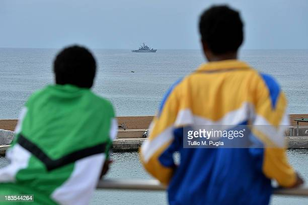 Surviving immigrants of the tragic shipwreck off the Italian coast look on as Italian Navy and Coast Guard units take part of search and rescue...