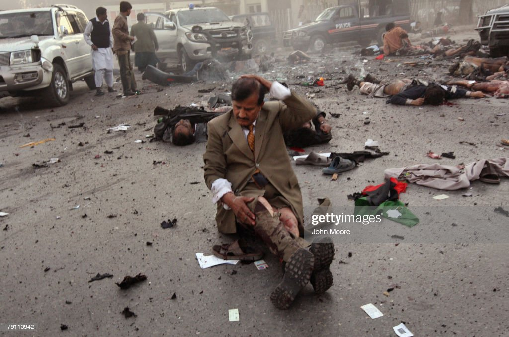A survivor awaits evacuation immediately after a blast attack on former Prime Minister Benazir Bhutto on December 27, 2007 in Rawalpindi, Pakistan. The opposition leader has died from a bullet wound to the neck after speaking at an election rally in the northern city where an estimated 15 people were left dead by the explosion, a party official and Bhutto's husband have been quoted as saying.