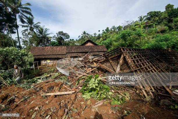 A survivor checks his damaged home after a wall of mud slammed onto houses from a hillside following heavy rainfall in Ponorogo district East Java on...