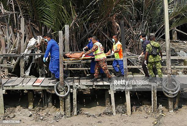 A survivor from a capsized immigrant boat is carried on a stretcher by Malaysian Fire and Rescue department members at Malaysia's western state of...