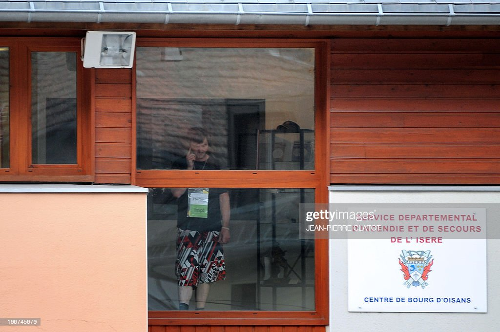 A survivor gives a phone call on April 16, 2013 inside the firefighters building in Bourg d'Oisan, where survivors of a coach crash have been sheltered. At least one person died and three others were seriously injured after a coach carrying Britons crashed in the French Alps, local officials said. The coach slammed into the mountain face bordering the winding road down from the popular ski resort of Alpe d'Huez and caught fire. An official told AFP one person -- thought to be the bus driver -- died, three others were seriously injured and 21 more slightly hurt. Police had previously said three perished in the accident.