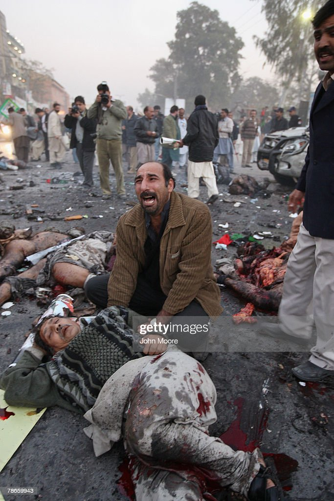 A survivor grieves over a wounded man following a bomb attack on former Prime Minister Benazir Bhutto on December 27, 2007 in Rawalpindi, Pakistan. The opposition leader has died from a bullet wound to the neck after speaking at a rally in the northern city where an estimated 15 people were left dead by the explosion, a party official and Bhutto's husband have been quoted as saying.