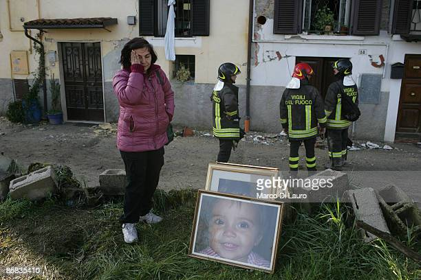 Survivor, helped by Italian fire fighters, recovers personal items on April 7, 2009 in Onna a village near L'Aquila, Italy. On April 6, 2009 the 6.3...