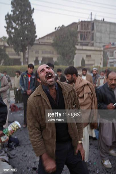 Survivor is overcome with emotion at the site of a bomb attack on former Prime Minister Benazir Bhutto on December 27, 2007 in Rawalpindi, Pakistan....
