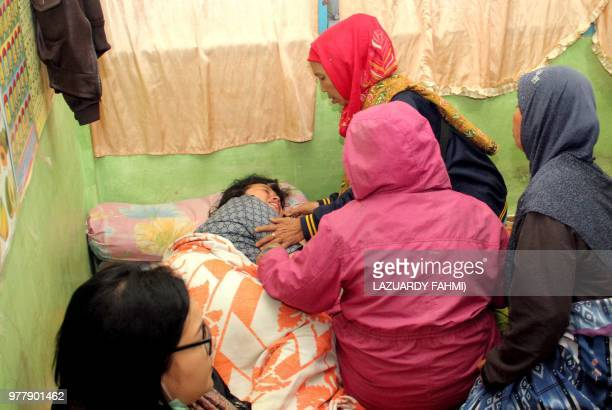 A survivor is surrounded by family members after she was rescued after a boat overturned on Lake Toba in the province of North Sumatra on June 18...