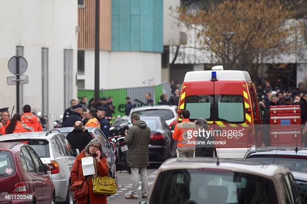 A survivor is talking on her mobile in front of the offices of the French satirical newspaper Charlie Hebdo on January 7 2015 in Paris France Armed...