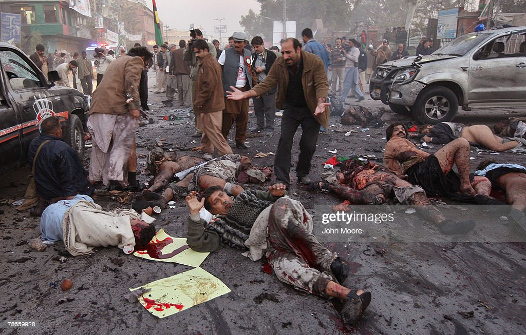 A survivor looks over the dead and wounded immediately after a bomb attack on former Prime Minister Benazir Bhutto December 27, 2007 in Rawalpindi, Pakistan. The opposition leader has died from a bullet wound to the neck after speaking at an election rally in the northern city where an estimated 15 people were left dead by the explosion, a party official and Bhutto's husband have been quoted as saying.