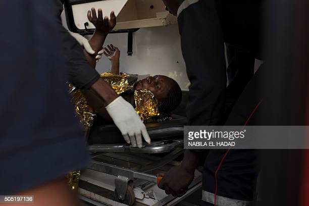 A survivor of an assault by AlQaeda linked gunmen on the Cafe Cappuccino is transported to the hospital in Ouagadougou on January 16 2016 Security...