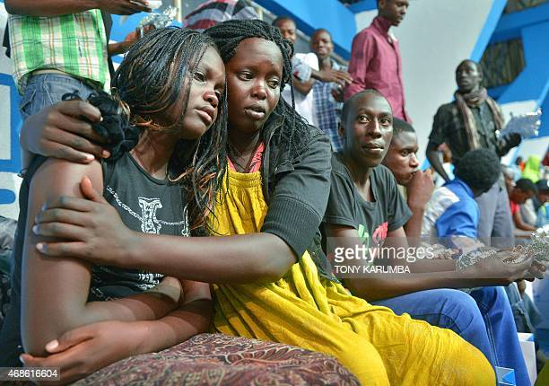 A survivor of an attack by islamist gunmen claimed by alShabab on a university campus in Garissa northern Kenya is comforted by a colleague after...