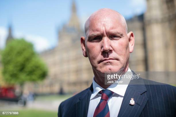 Survivor of the 1982 IRA Hyde Park bomb attack Simon Utley poses for a photograph in front of the Houses of Parliament on April 25 2017 in London...