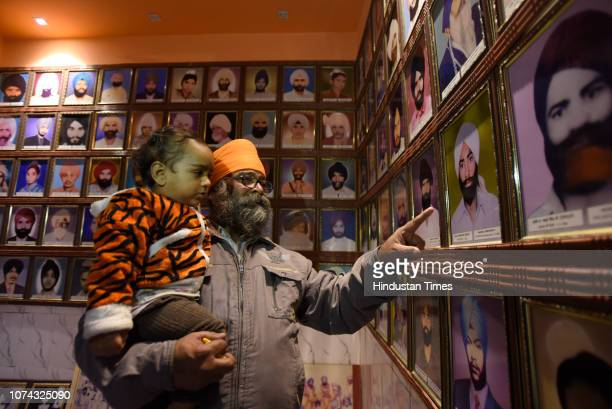 A survivor of the 1984 Sikh massacre looks at the portraits of the people who were killed during the massacre at Trilokpuri on December 17 2018 in...