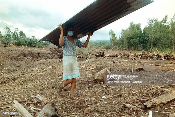 A survivor of the deadly mudslide on Casitas volcano carries a sheet of iron to make a shelter