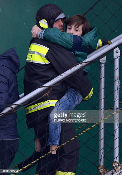 A survivor of the ferry 'Norman Atlantic' is carried by a rescuer as he disembarks from the ship 'Siprit of Piraeus' after arriving in the harbor of...