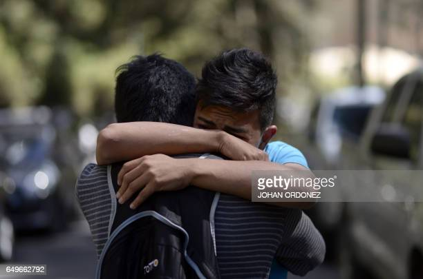 A survivor of the fire embraces a relative outside the children's shelter Virgen de la Asuncion after a fire at the facility killed at least 19...