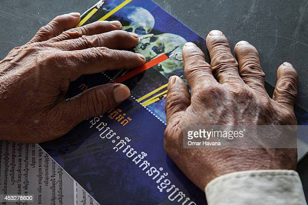 A survivor of the Khmer Rouge regime holds a magazine during the pronouncement of the verdict for former Khmer Rouge leaders Nuon Chea and Khieu...