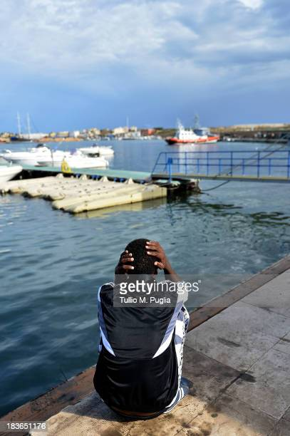 A survivor of the shipwreck of immigrants off the Italian coast looks out over the water of Lampedusa on October 8 2013 in Lampedusa Italy The search...