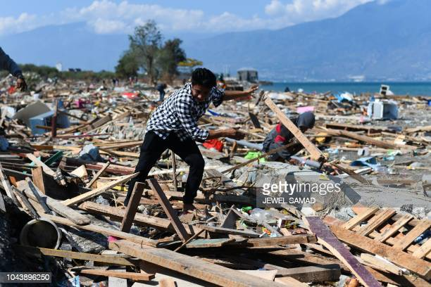 A survivor salvages useable items from debris in Palu Indonesia's Central Sulawesi on October 1 after an earthquake and tsunami hit the area on...